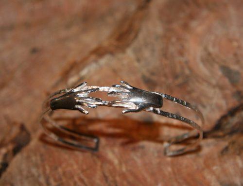 Zilveren gehamerde armband met handjes